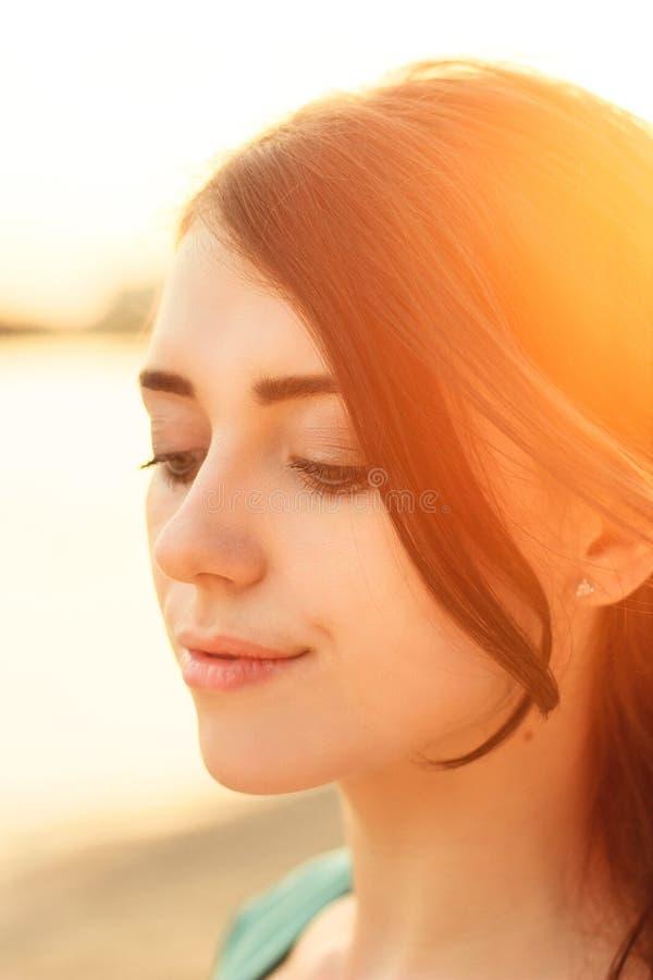 日落的美丽的女孩 免版税库存图片