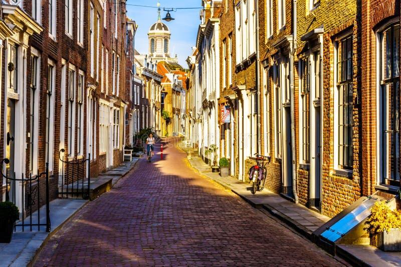 日落的荷兰骑自行车的人在狭窄的街道在历史名城西兰省省的米德尔堡,荷兰 免版税库存照片