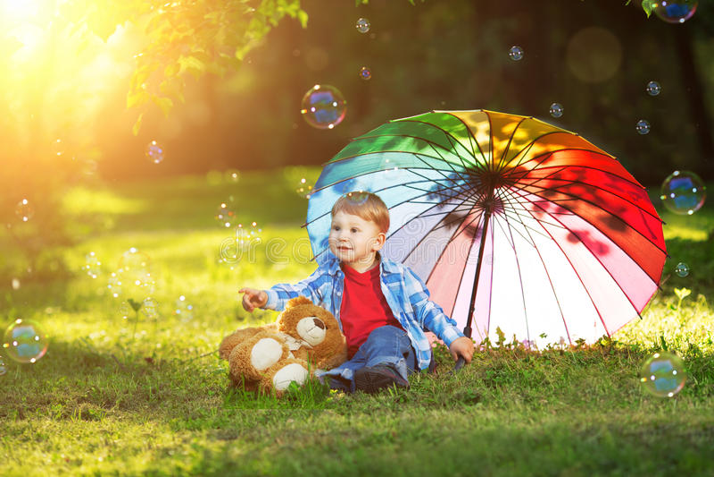 日落的,后面光一个孩子 在草甸的孩子在公园 Th 库存照片