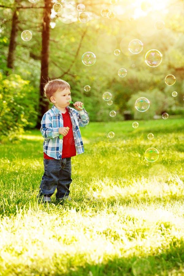 日落的,后面光一个孩子 在草甸的孩子在公园 Th 免版税库存图片