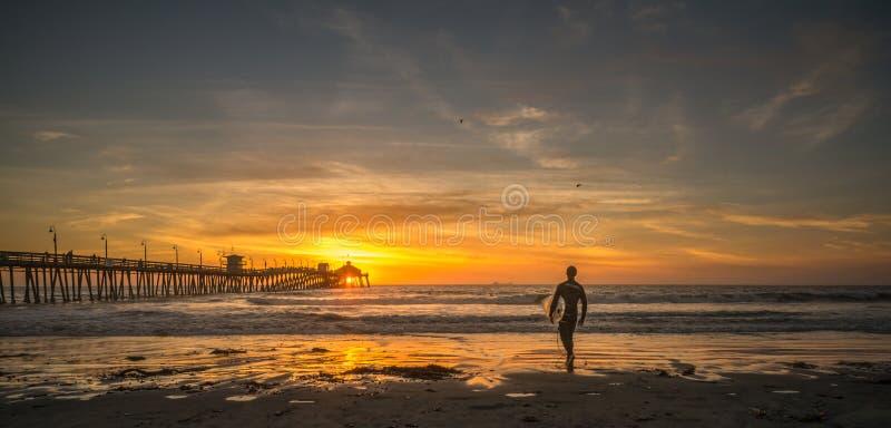 日落皇家海滩码头的剪影冲浪者 免版税图库摄影