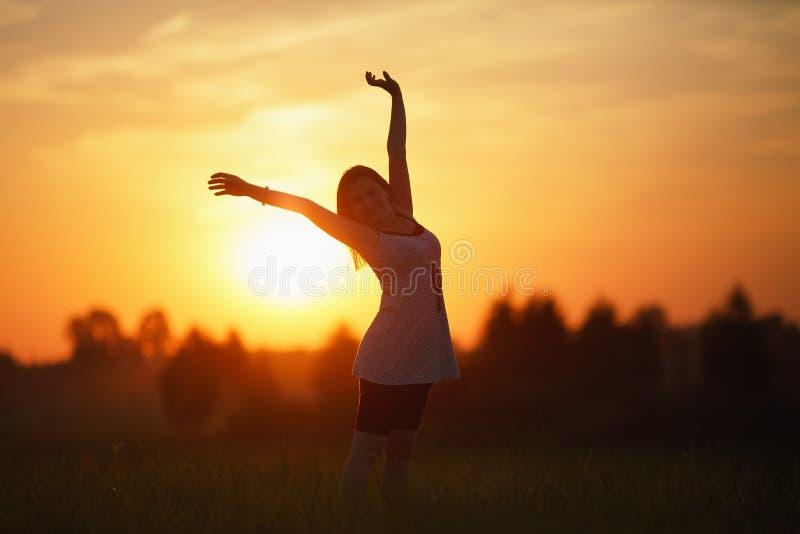 日落背景的妇女 免版税图库摄影
