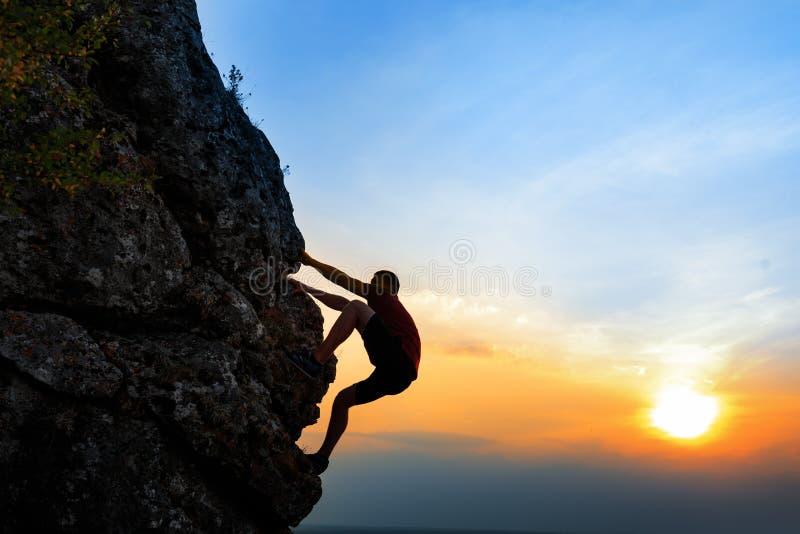 日落背景的攀岩运动员 体育运动和有效的寿命 免版税库存照片