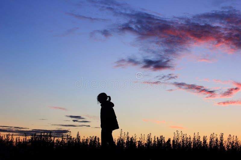 日落背景的,剪影哀伤的女孩 库存照片