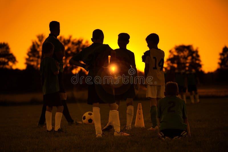 日落足球 孩子足球在训练的橄榄球队与教练 免版税库存图片