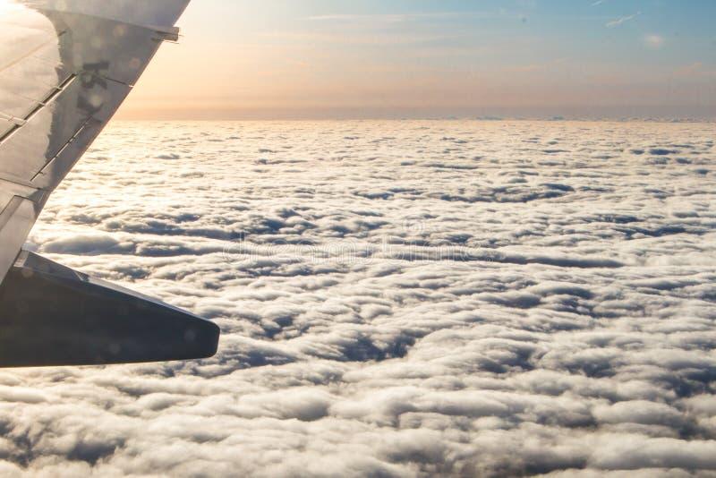 日落通过在云彩上的飞机窗口 免版税库存图片