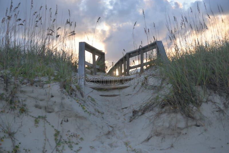 日落通过带领到/从海滩的木板走道的木打桩偷看 图库摄影