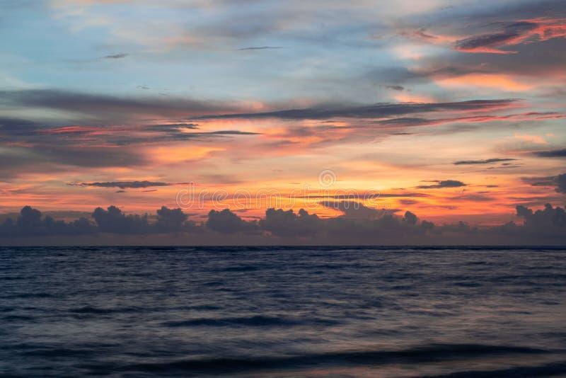 日落阴云密布天空,橙色光,风平浪静波浪 免版税图库摄影