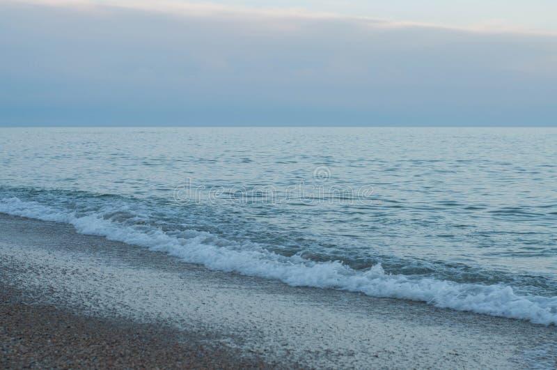 日落风平浪静海浪在紫罗兰色黄昏晚上 库存照片