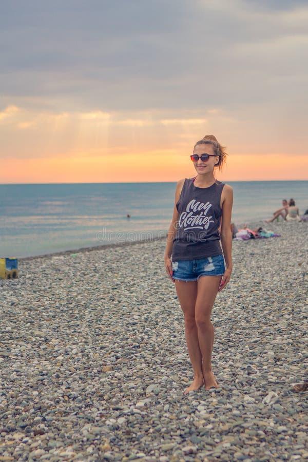 日落黎明 站立在一个被环绕的小卵石石头的少妇 女孩享用异常的海滩,在岸的小卵石  免版税库存图片
