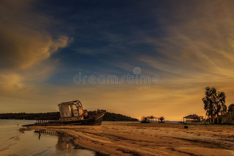 日落,在一个离开的海滩的被放弃的老小船 库存图片