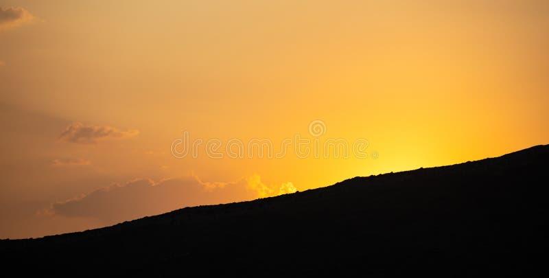 日落,在山剪影的日出 在天空背景,空间,横幅的疏散云彩 图库摄影