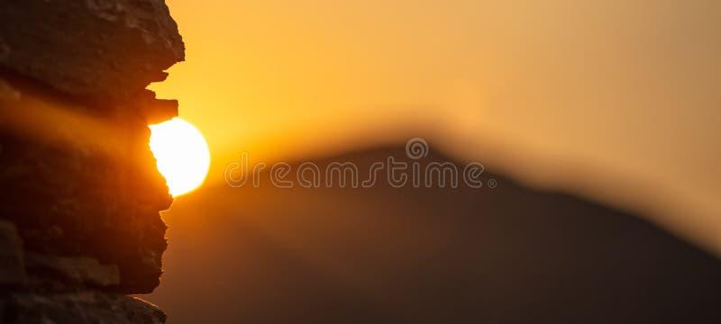 日落,在蓝色山剪影的日出 在岩石后的太阳,天空背景,空间,横幅 免版税图库摄影