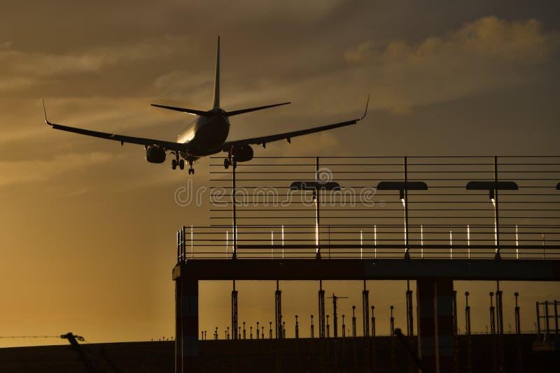 日落,当一架商业喷气机 免版税库存图片