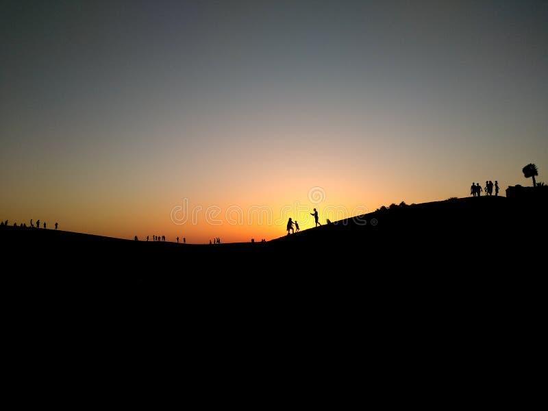 日落,当太阳在天际显示黑剪影后我们哪里能看到不同的人享用 库存照片
