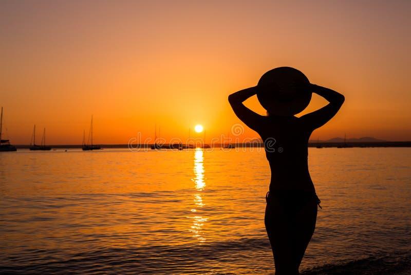 日落,性感的妇女剪影 享受在海滩的无忧无虑的妇女日落 r r ES Prenc海滩 免版税库存图片