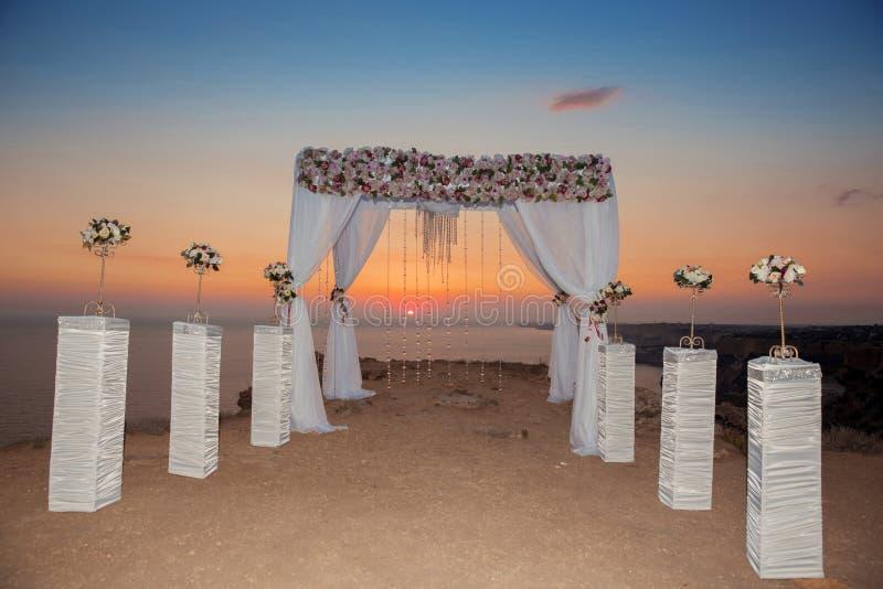 日落 与花装饰arrangemen的婚礼曲拱 免版税库存照片
