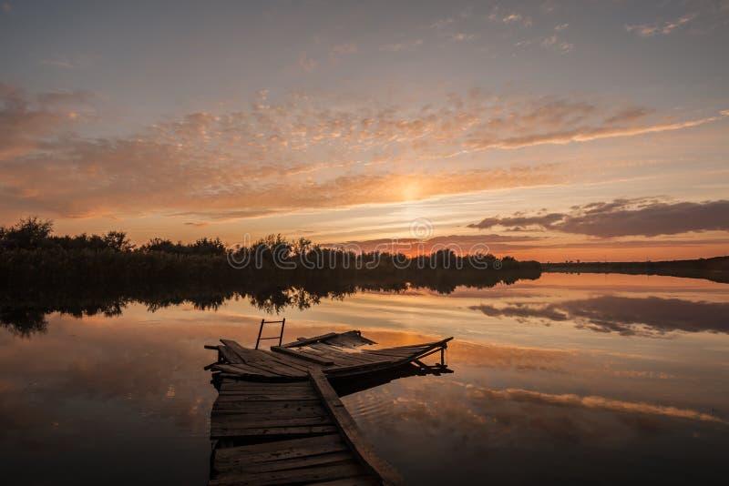 日落 云彩的反射在河水的 游泳和钓鱼的木桥 免版税库存照片