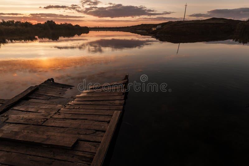 日落 云彩的反射在河水的 游泳和钓鱼的木桥 库存照片