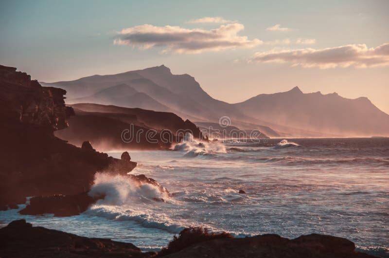 日落 蓝色横向海洋掌上型计算机天空 岩石和波浪与雾 图库摄影
