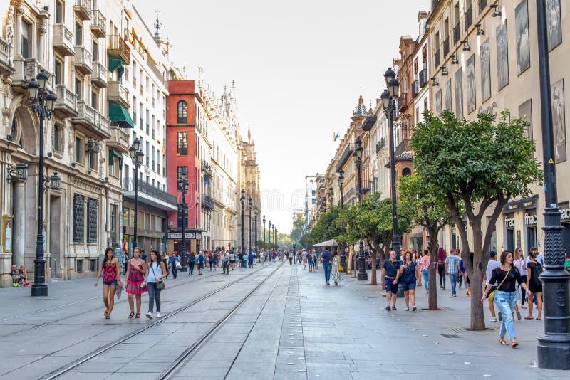 日间走在一条步行街道的人们在大教堂附近在塞维利亚,西班牙 著名地标 免版税库存照片
