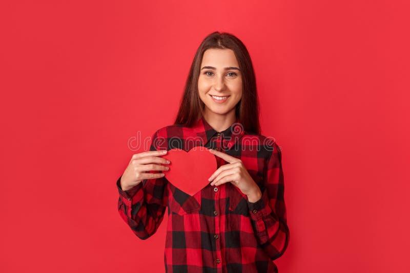 日s华伦泰 在与心脏卡片微笑的红色隔绝的年轻女人身分愉快对照相机 免版税库存照片