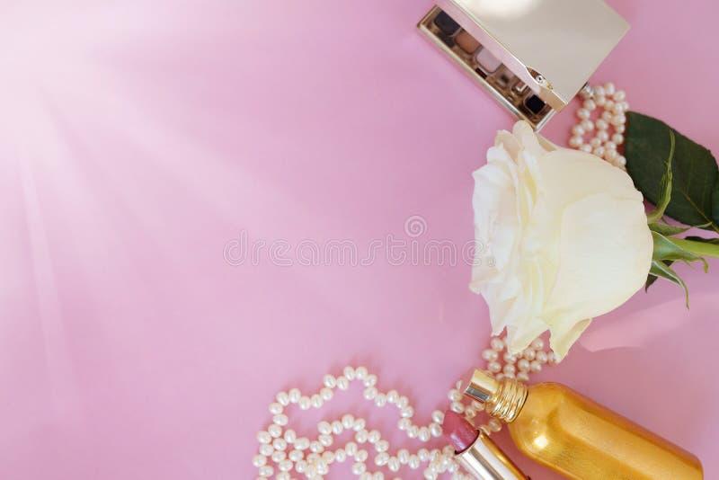 日s华伦泰 女性辅助部件,首饰,香水瓶,与丝带,珍珠,在桃红色的柔和的玫瑰的礼物 免版税库存照片