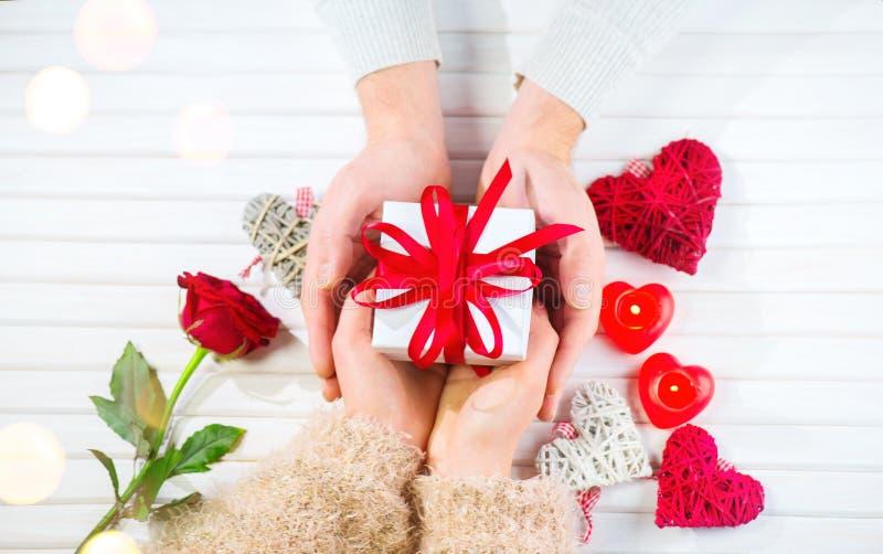 日s华伦泰 年轻夫妇递拿着在白色木背景的礼物盒 概念亲吻妇女的爱人 库存图片
