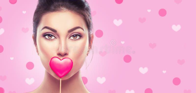 日s华伦泰 秀丽年轻时装模特儿女孩用在桃红色的华伦泰心形的曲奇饼 免版税图库摄影