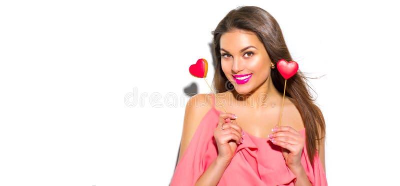 日s华伦泰 秀丽快乐的年轻时装模特儿女孩用华伦泰心形的曲奇饼 库存图片
