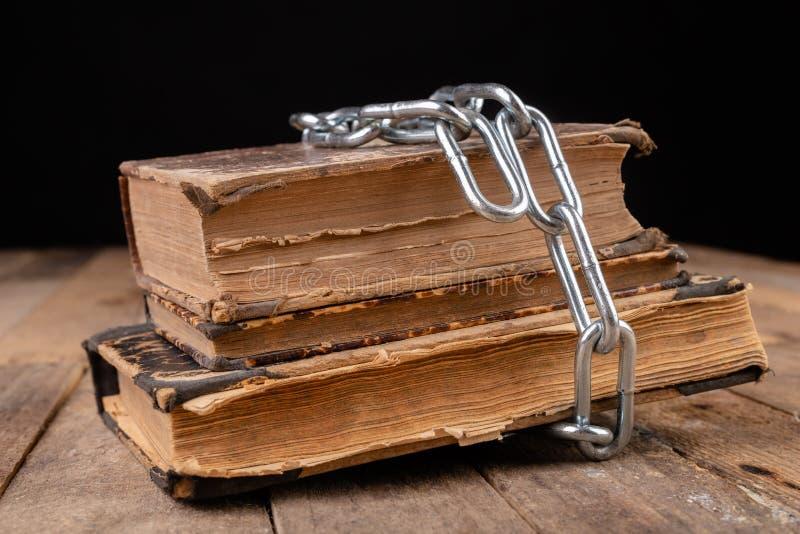 旧书与一个新的发光的链子有关 在一张木桌上的禁止的老工作艺术家 免版税库存照片