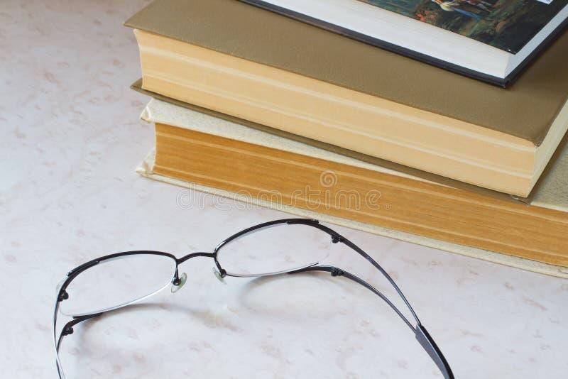 旧书和玻璃在桌面上 免版税库存图片
