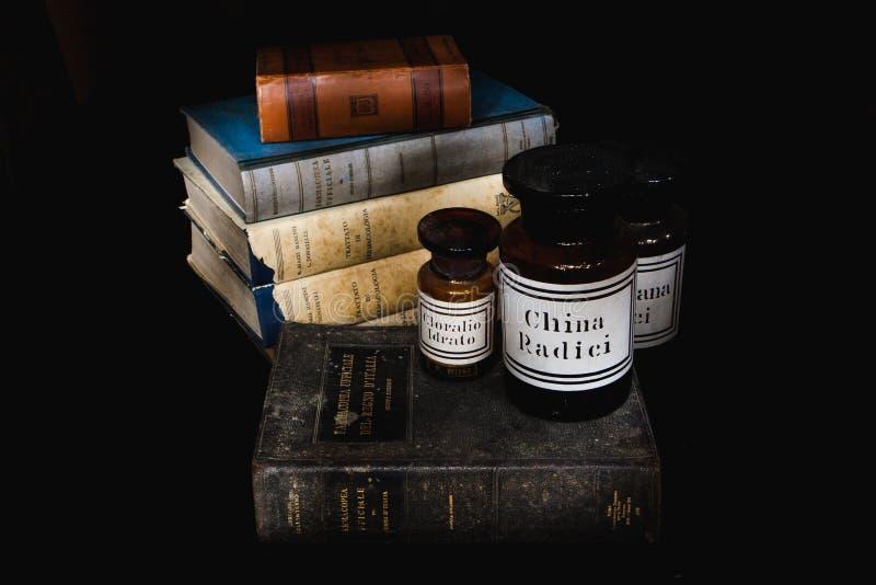 旧书意大利药典和药理书和老玻璃药房花瓶拔地响,氯荃,奎宁 轻的绘画 库存照片