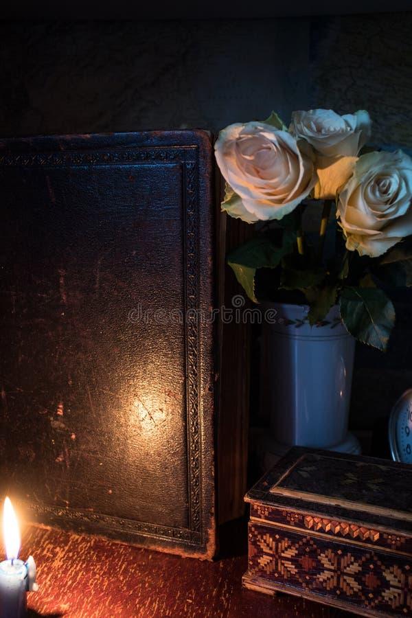 旧书花和箱子在蜡烛光下 库存图片