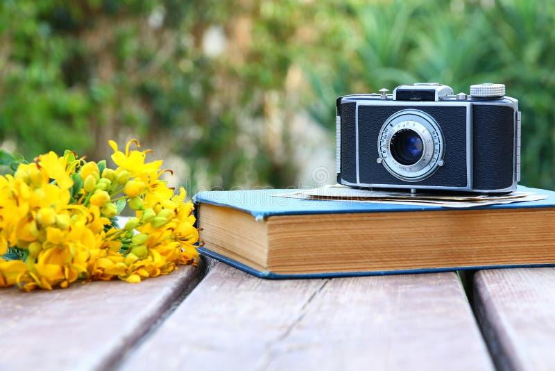 旧书,葡萄酒在领域旁边的照片照相机开花 免版税库存照片