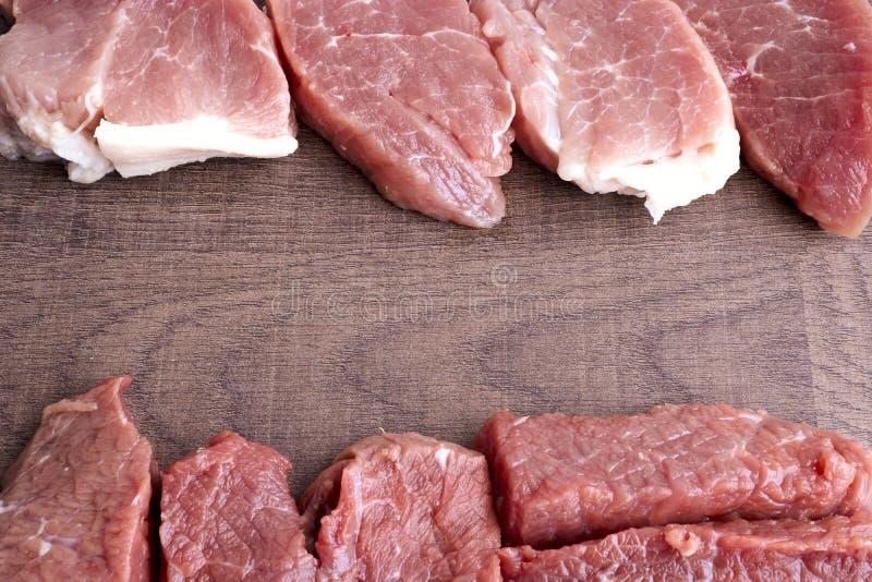 旧木板上大片牛肉和猪肉 烹前生肉 胆固醇食品的概念 免版税库存图片