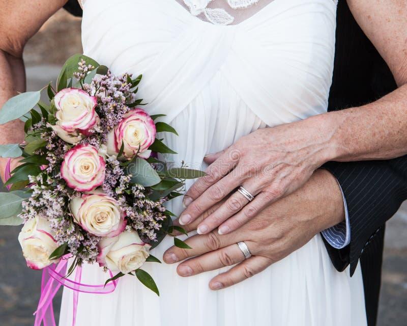 更旧的新娘和新郎手和圆环与花 库存照片