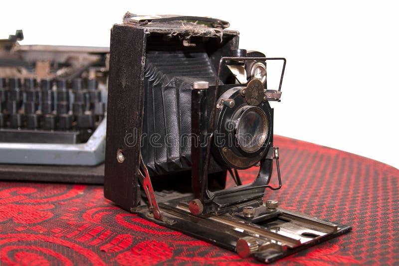 破旧的老照片照相机和打字机在红色桌布iso 免版税库存照片