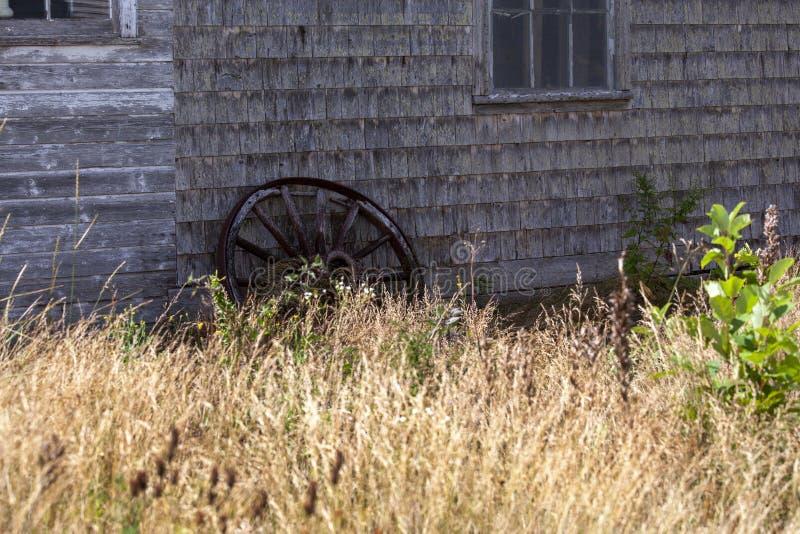 旧货车轮对着谷仓 免版税库存图片