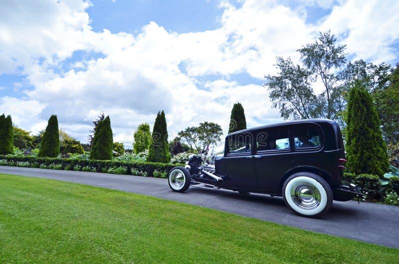 旧车改装的高速马力汽车新娘汽车到达庭院婚礼 免版税库存图片