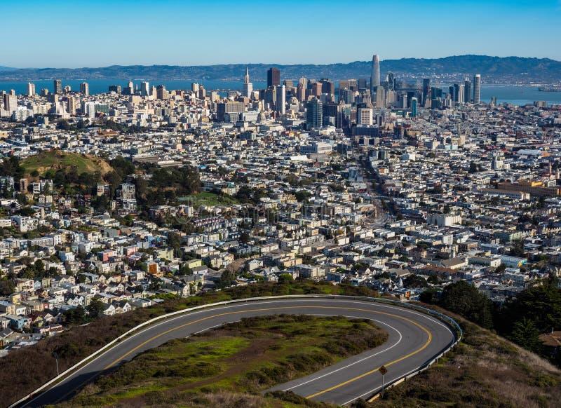 旧金山地平线,与弯曲路,从双峰顶的看法的都市风景 免版税库存照片