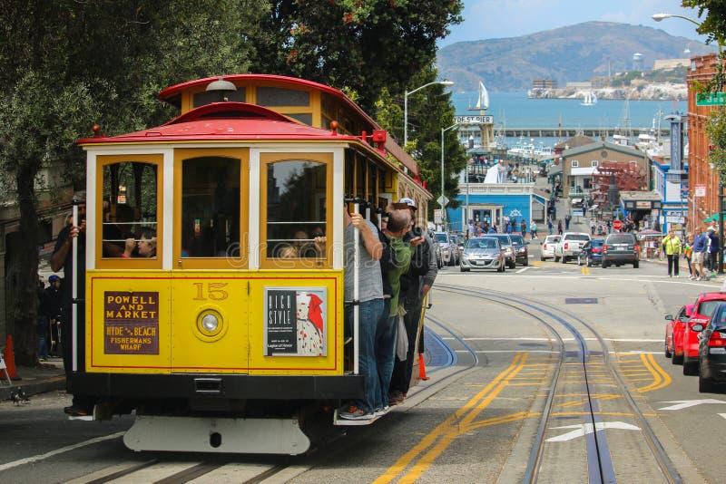 旧金山,加利福尼亚- Mai 23日2015年:乘坐在偶象缆车,在海德街视图overloo顶部的蓝天天的游人 库存图片