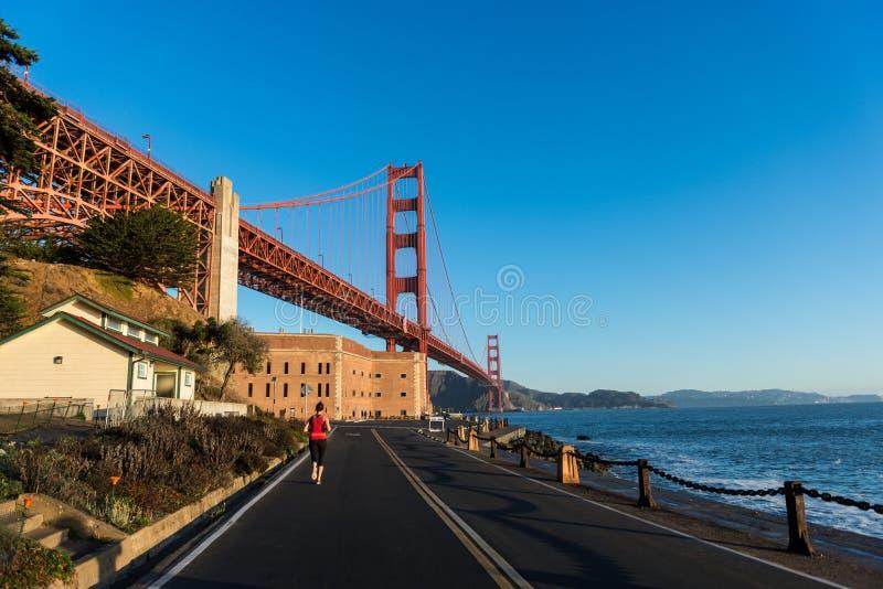 旧金山,美国- 2018年10月12日:在堡垒点的妇女赛跑与金门大桥在背景中 免版税库存图片