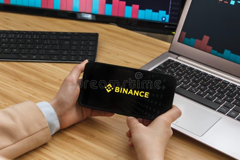 旧金山,美国- 2019年6月18日:拿着智能手机的女性贸易商手使用Binance Cryptocurrency交换的应用 免版税库存照片