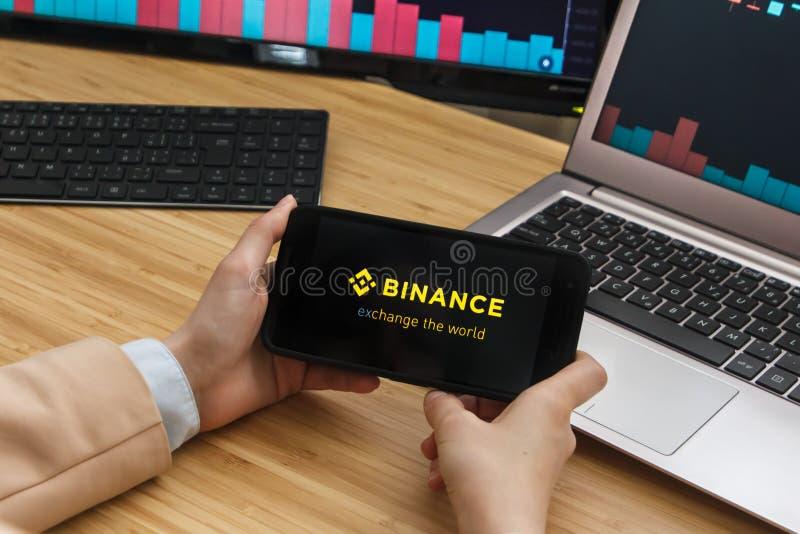 旧金山,美国- 2019年6月18日:拿着智能手机的女性贸易商手使用Binance Cryptocurrency交换的应用 库存照片