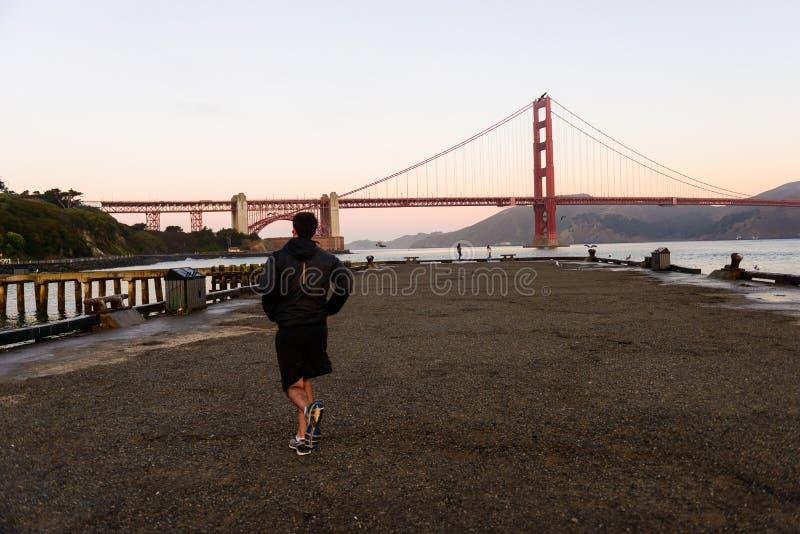 旧金山,美国- 2018年10月12日:跑在鱼雷码头的日出,旧金山的一个人 免版税库存照片