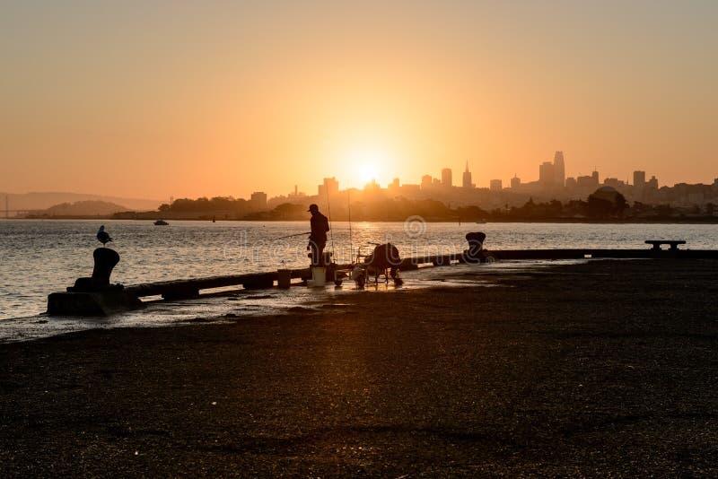 旧金山,美国- 2018年10月12日:钓鱼在日出的一个人的剪影有街市背景在旧金山 免版税库存图片