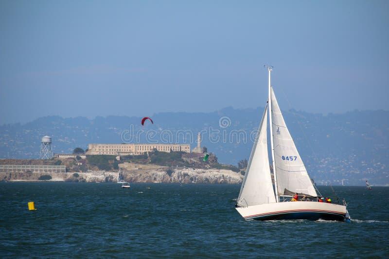 旧金山,美国- MAI 23日2015年:在Alcatraz监狱海岛前面的游艇风帆 免版税库存照片