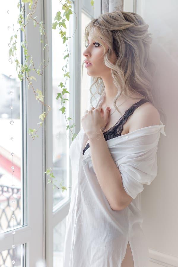 早上,窗边漂亮可爱的女孩穿着白色衬衫,带着咖啡 库存照片