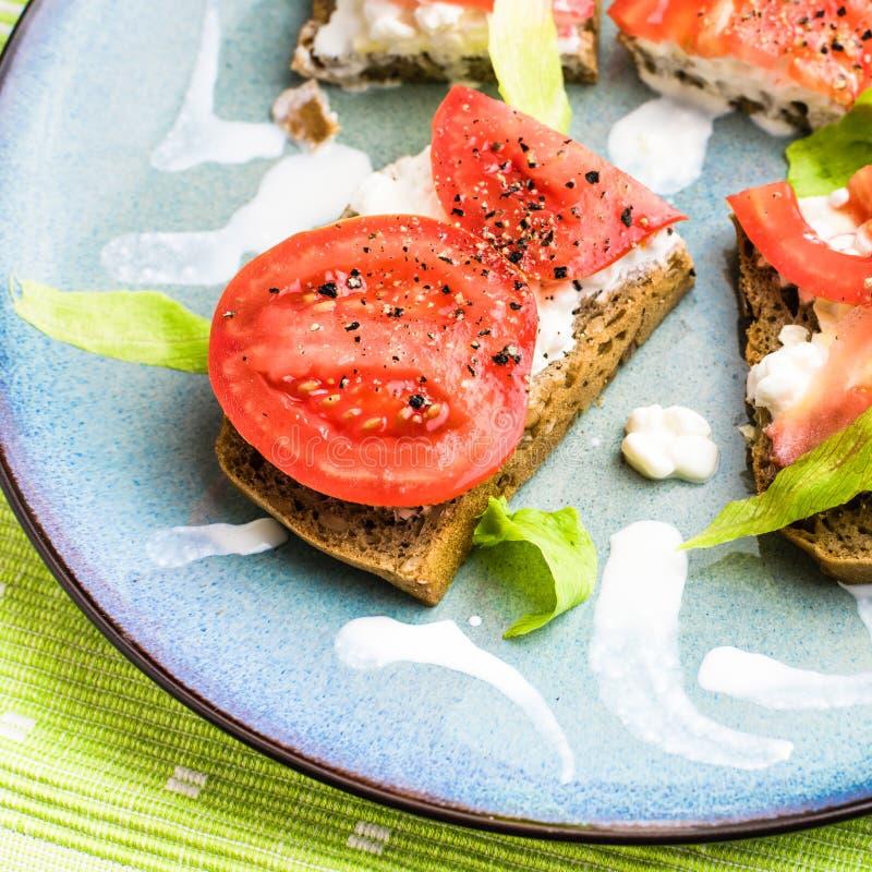 早午餐-全麦面包三明治用蕃茄、酸奶干酪和莴苣 库存照片
